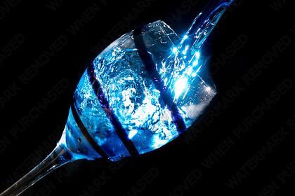 KU8C8797-Edit   Blue water being pored into a wine glass creating a splash.   Keywords: blue water glass swirl star burst macro light freeze black back ground wine austen blakemore